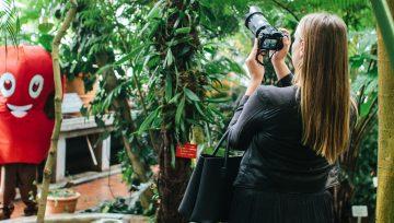 Nainen kuvaamassa puiden välistä henkilöä, jolla on yllään kasvis-puku