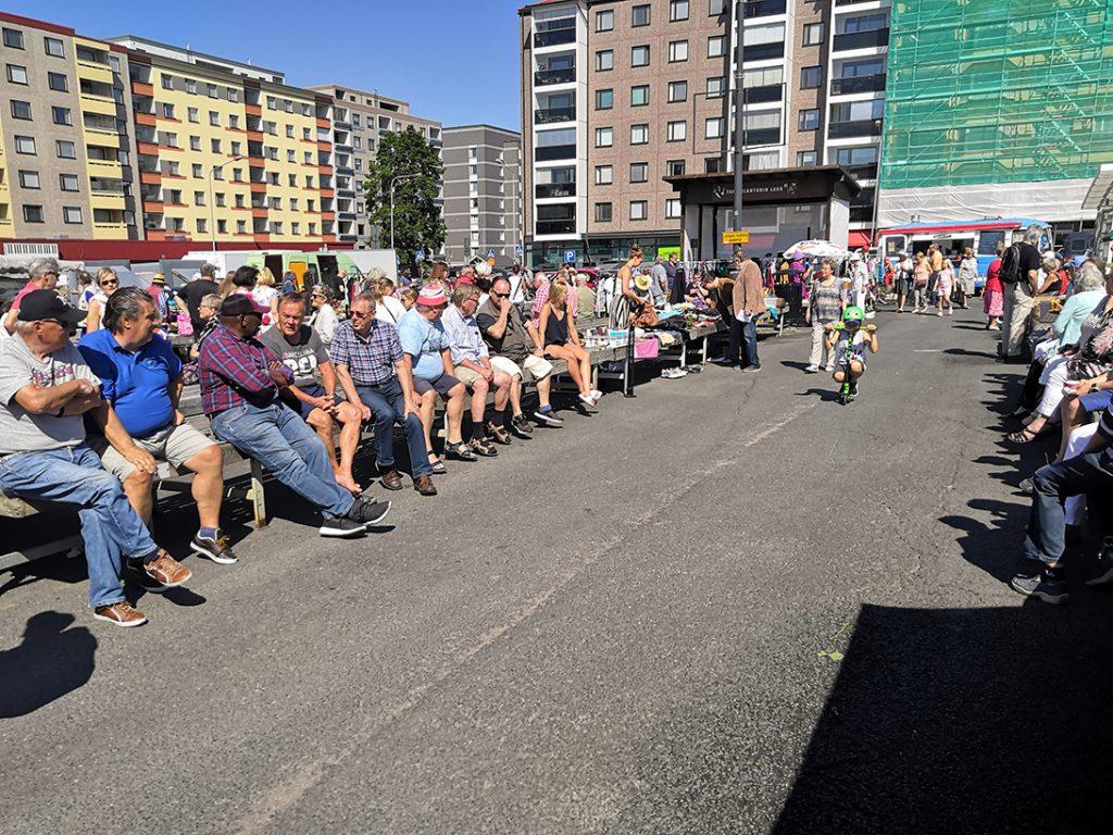 Ihmiset istuvat aurinkoisella torilla Tampereella.